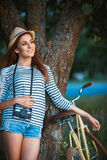 Lovely young woman in a hat with a bicycle in a park Royalty Free Stock Photos