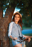 Lovely young woman in a hat with a bicycle in a park Royalty Free Stock Photography