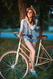 Lovely young woman in a hat with a bicycle in a park Stock Images