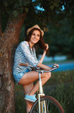 Lovely young woman in a hat with a bicycle in a park Stock Photos