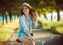 Lovely young woman in a hat riding a bicycle outdoors. Active pe Royalty Free Stock Photo