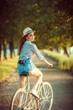 Lovely young woman in a hat riding a bicycle outdoors. Active pe Royalty Free Stock Photos