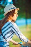 Lovely young woman in a hat riding a bicycle outdoors. Active pe Royalty Free Stock Image
