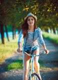 Lovely young woman in a hat riding a bicycle outdoors. Active pe Stock Image