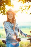 Lovely young woman in a hat riding a bicycle outdoors. Active pe Royalty Free Stock Photography