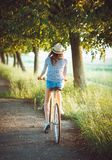 Lovely young woman in a hat riding a bicycle outdoors. Active pe Stock Photo