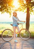Lovely young woman in a hat riding a bicycle outdoors. Active pe Stock Images