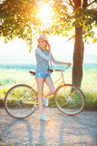 Lovely young woman in a hat riding a bicycle in a park Royalty Free Stock Image