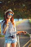 Lovely young woman in a hat riding a bicycle in a park Stock Photography