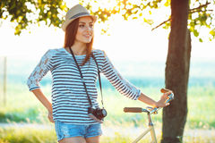 Lovely young woman in a hat riding a bicycle in a park Royalty Free Stock Photography