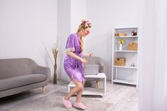 Girl dancing in living room. Lovely young woman having fun dancing at home. Adorable young lady with curled hair wearing home comfy clothing and cute slippers stock photography