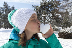 Lovely young woman kissing snow heart Royalty Free Stock Image