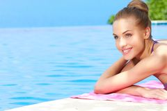 Lovely Young Woman Laying Prone at Poolside. Close up Lovely Slim Young Woman Laying Prone at the Side of Enchanting Pool Stock Photo