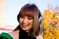 Lovely young woman listening music in headphones. Outdoors Stock Image