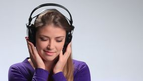 Lovely young woman listening music in headphones stock footage