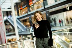 Lovely young woman looking on mobile phone in shopping center. Portrait of lovely young woman looking on mobile phone in shopping center stock photos
