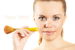 Lovely young woman with a make-up brush. Isolated. royalty free stock images