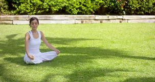 Lovely young woman meditating in the garden stock video