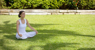 Lovely young woman meditating in the garden Stock Photography
