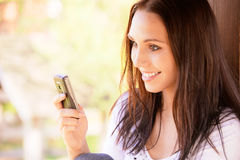 Lovely young woman reads sms. On mobile phone Royalty Free Stock Image