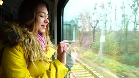 Lovely young woman riding in train and looking at  landscape outside  railway transport window in  autumn afternoon. Portrait of cute girl who watches over stock footage