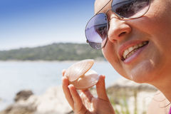 Lovely young woman with seashell on the sea coast Stock Photos