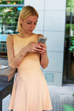 Lovely young woman sending text message with her mobile phone Royalty Free Stock Image