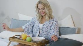 Smiling woman having breakfast in bed stock footage