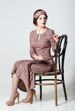 Lovely young woman sitting on chair. Portrait in retro style Stock Image
