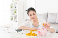 Lovely young woman sitting in living room  at home. And holding gold coin saving money into pink piggy bank for buying new house with family Stock Image