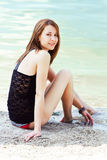 Lovely young woman sitting near the water Stock Photos