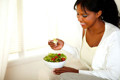 Lovely young woman smiling and looking to salad Royalty Free Stock Photos