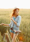 Lovely young woman stands in a field with her bicycle Royalty Free Stock Images