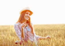 Lovely young woman stands in a field with her bicycle Royalty Free Stock Photo