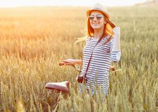 Lovely young woman stands in a field with her bicycle Royalty Free Stock Photos