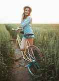 Lovely young woman stands in a field with her bicycle Stock Image