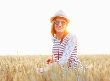 Lovely young woman stands in a field with her bicycle Stock Photos