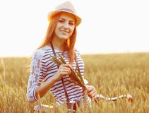 Lovely young woman stands in a field with her bicycle Stock Images