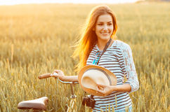 Lovely young woman stands in a field with her bicycle Stock Photo
