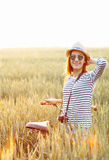 Lovely young woman stands in a field with her bicycle Royalty Free Stock Image