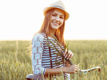 Lovely young woman stands in a field with her bicycle Royalty Free Stock Photography