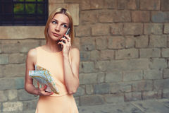 Lovely young woman talking on cell phone while standing in the city street in summer stock image