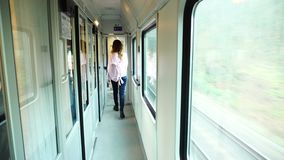 Lovely young woman travels along  corridor of moving train, heading for  exit in  morning. stock footage