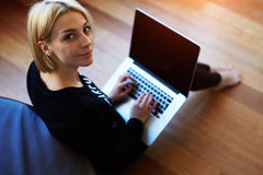 Lovely young woman working on laptop computer at home. Attractive blonde hair student using laptop in her living room and look to the camera, female freelancer
