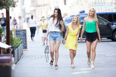 Girls are back in town. Lovely young women having fun in the city streets Stock Images