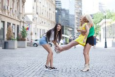 Girls are back in town. Lovely young women having fun in the city streets Stock Photos