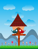 Lover Birds bird perched on a bird house with landscape of blue sky - full color Stock Image