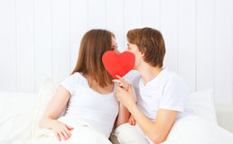 Lover couple kissing with a red heart in bed. Concept for Valentine's Day. lover couple kissing with a red heart in bed Stock Images