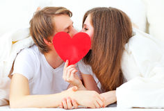 Lover couple kissing with a red heart in bed Royalty Free Stock Images