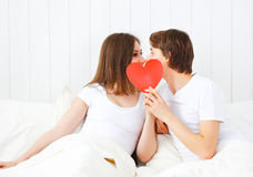 Lover couple kissing with a red heart in bed Stock Photo
